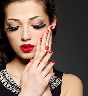 Mujer de moda con maquillaje creativo moderno con manicura roja de pestañas postizas