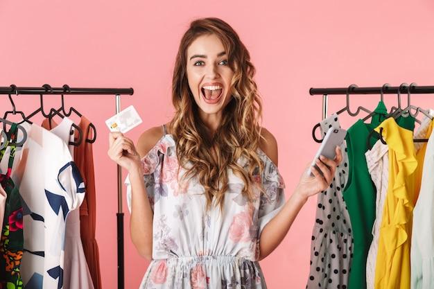 Mujer de moda de pie cerca del armario mientras sostiene el teléfono inteligente y la tarjeta de crédito aislado en rosa