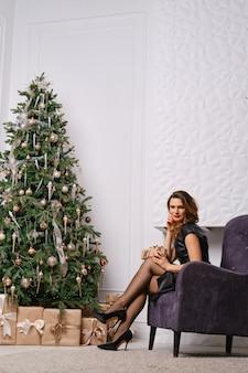 Mujer de moda posando en un sillón cerca del árbol de navidad y la chimenea, mostrando las piernas con medias pasadas de moda