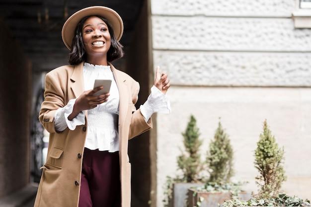 Mujer de moda sonriente que sostiene su teléfono