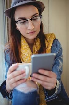Mujer de moda mediante teléfono móvil en la cafetería