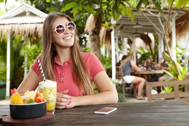 Mujer de moda en tonos redondos sonriendo felizmente mientras desayuna en el restaurante en la acera, sentado en la mesa de madera con batido fresco