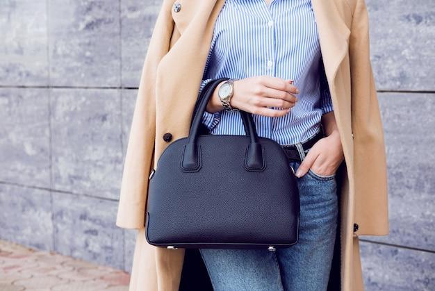 Mujer de moda traje en elegante abrigo beige y jeans con bolso negro grande
