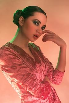 Mujer modelo de alta moda en coloridas luces brillantes posando