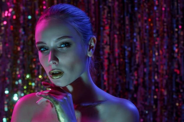 Mujer modelo de alta moda en coloridas luces de neón brillantes posando en estudio, club nocturno. retrato de la hermosa bailarina sexy seductora chica en uv.