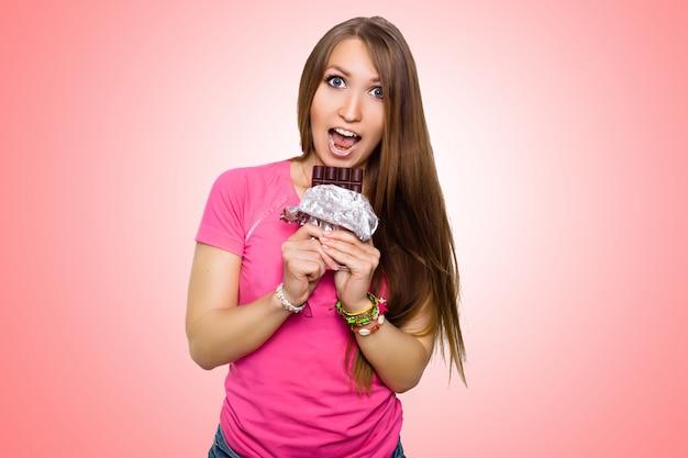 Mujer modelo de belleza comiendo chocolate negro. hermosa joven sorprendida toma dulces de chocolate, sonriendo y divirtiéndose