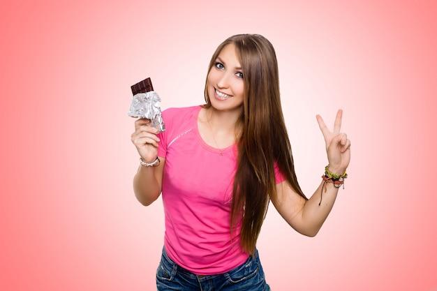 Mujer modelo de belleza comiendo chocolate negro. hermosa joven sorprendida toma dulces de chocolate
