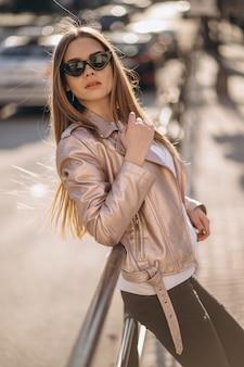 Mujer modelo de pie junto a la carretera.