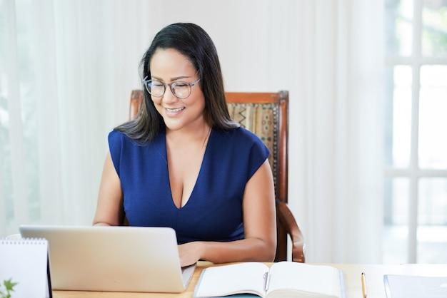 Mujer moderna adulta que trabaja en la computadora portátil en la oficina