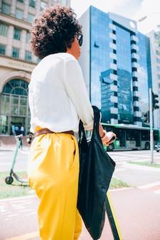 Mujer moderna en una ciudad con un patinete eléctrico