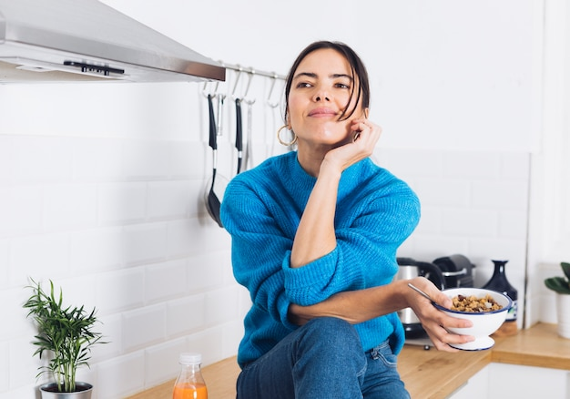 Mujer moderna desayunando en la cocina