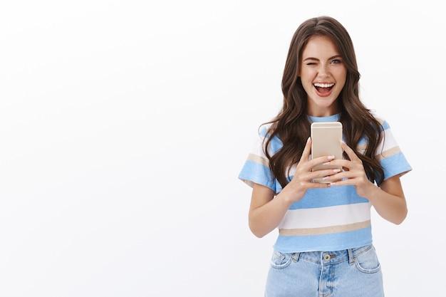Mujer moderna con estilo descarado que toma selfie en el espejo, guiñando un ojo ambicioso y coqueto mostrar la lengua, sonriendo encantada, prueba la nueva cámara del teléfono inteligente, fotografiando cerca de la pared blanca