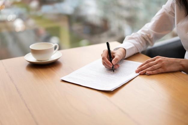Mujer moderna irreconocible tomando notas