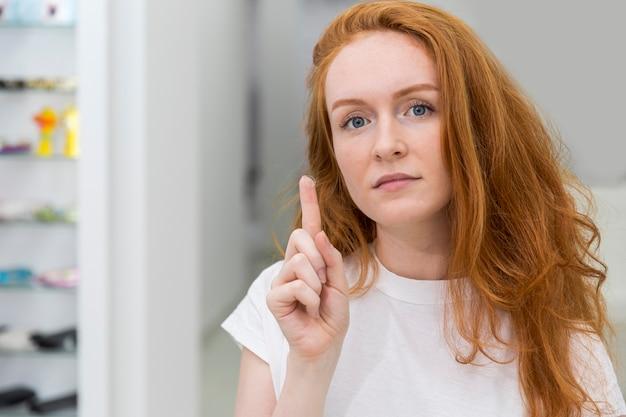Mujer moderna joven atractiva que muestra la lente de contacto y que mira la cámara
