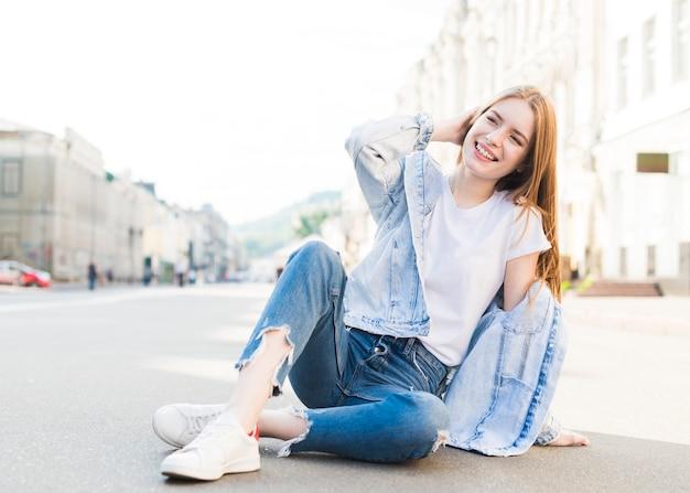 Mujer moderna joven elegante que se sienta en el camino y la presentación