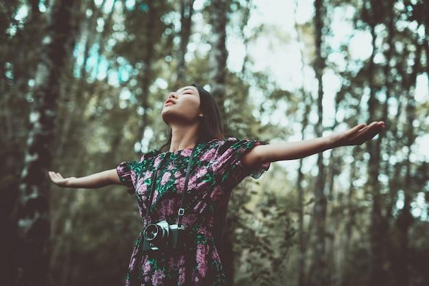 Una mujer moderna de pie en brazos con felicidad en el bosque.