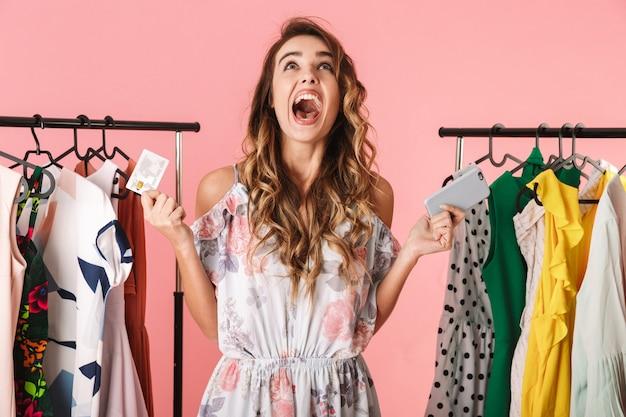 Mujer moderna de pie cerca del armario mientras sostiene el teléfono inteligente y la tarjeta de crédito aislado en rosa