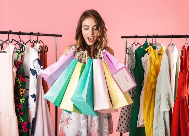Mujer moderna de pie en la tienda cerca de perchero y sosteniendo coloridas bolsas de compras aisladas en rosa