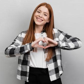Mujer moderna que muestra gesto del corazón