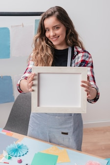Mujer moderna que muestra el marco vacío blanco