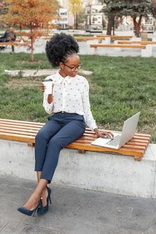 Mujer moderna que sostiene una taza de café mientras mira a su computadora portátil