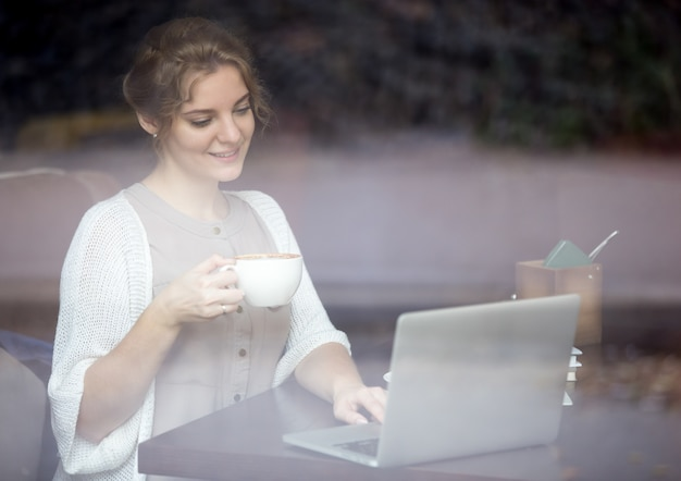 Mujer moderna que trabaja en la computadora portátil en cafetería. disparo a través de la ventana