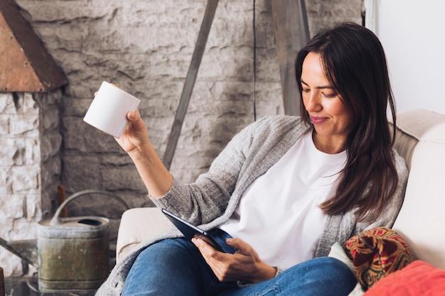 Mujer moderna sentada en el sofá usando la tablet