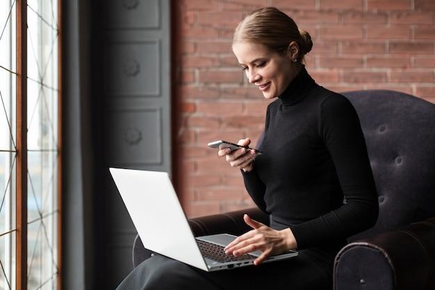 Mujer moderna sonriente que trabaja en la computadora portátil