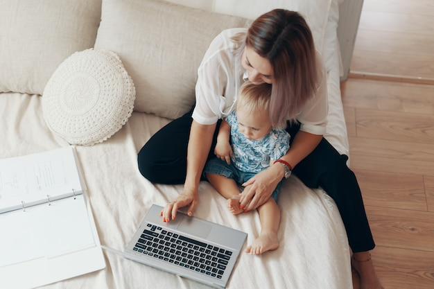 Mujer moderna trabajando con niños. concepto multitarea, freelance y maternidad