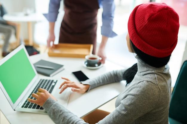 Mujer moderna usando laptop en café