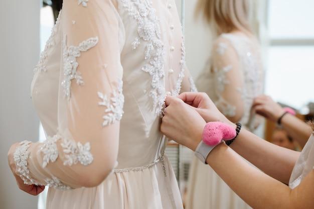Mujer con modista haciendo un toque final en la tienda de ropa de novia