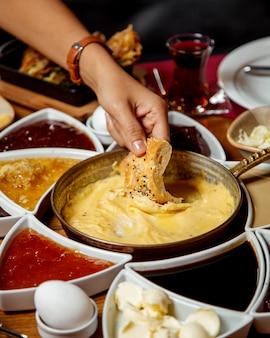 Mujer mojando pan en plato de queso derretido turco servido para el desayuno