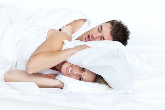 Mujer molesta en la cama con su novio roncando