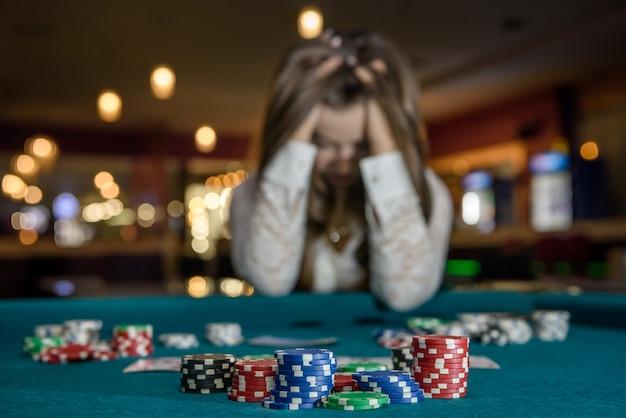 Mujer molesta en casino sentado detrás de la mesa de póquer