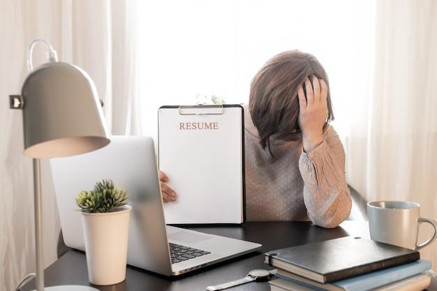 Mujer molesta cerró la cara de las manos cerca de su lugar de trabajo con la computadora portátil y reanudar la aplicación.
