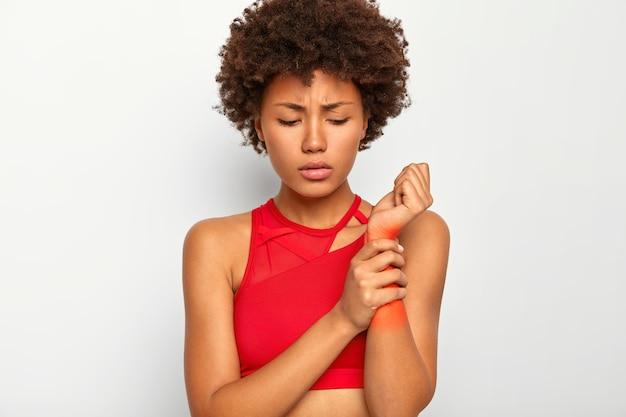 Mujer molesta y disgustada toca la mano lesionada, muestra una zona dolorosa problemática en la muñeca marcada con rojo, vestida con un top informal, sufre de un dolor terrible