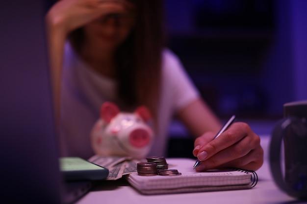 Mujer molesta se inclinó sobre el presupuesto familiar y el dinero