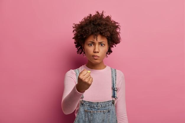 Mujer molesta insatisfecha con cabello afro sonríe y aprieta los puños, mira enojada a alguien, promete venganza o castigo por su mal comportamiento, tiene expresión de enojo, posa sobre una pared rosada
