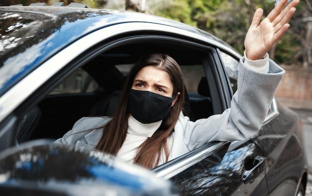 Mujer molesta con máscara facial regañando al conductor, sentado en el automóvil y mirando por la ventana, discutiendo con la persona en el automóvil que está adelante