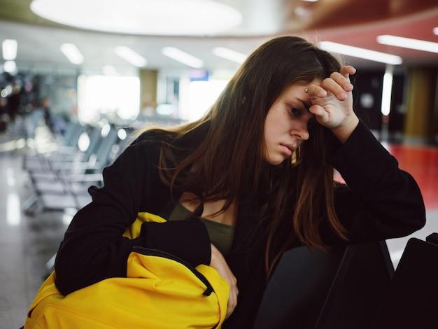 Mujer molesta con mochila amarilla se sienta en el aeropuerto mientras espera un vuelo