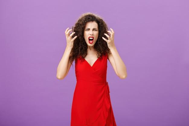 Mujer molesta y molesta a los empleados estropeando su actuación. retrato de músico femenino furioso indignado en vestido de noche rojo levantando puños apretados haciendo muecas y gritando enojado. copia espacio