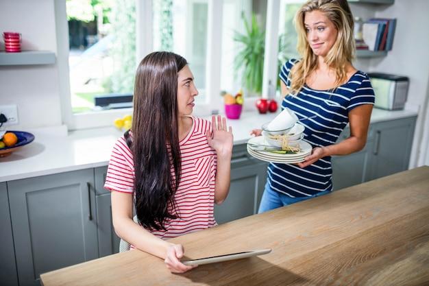 Mujer molesta que muestra platos sucios a un amigo en la cocina