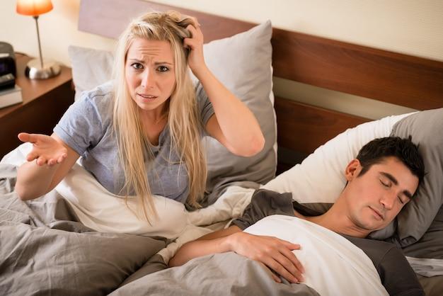 Mujer molesta por los ronquidos de su pareja.