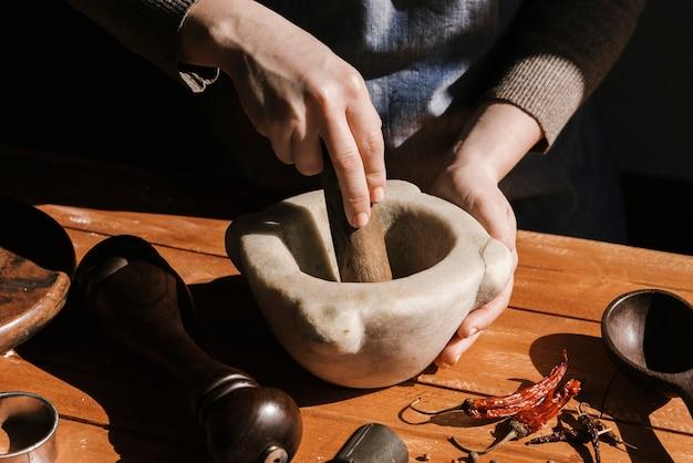 Mujer moliendo pimienta a mano