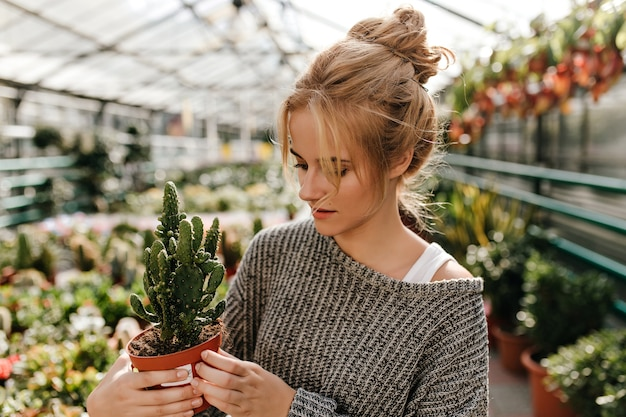 Mujer con moño mira cactus en maceta con interés, caminando por la galería con plantas.