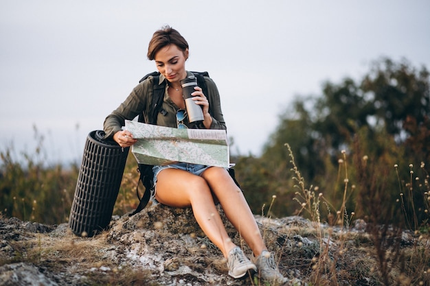 Mujer en montaña con bolsa de viaje mirando el mapa