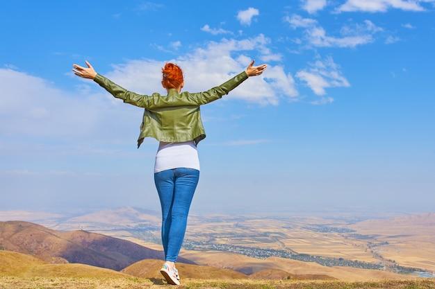 Mujer en una montaña con los brazos extendidos en celebración de un hermoso día soleado de verano