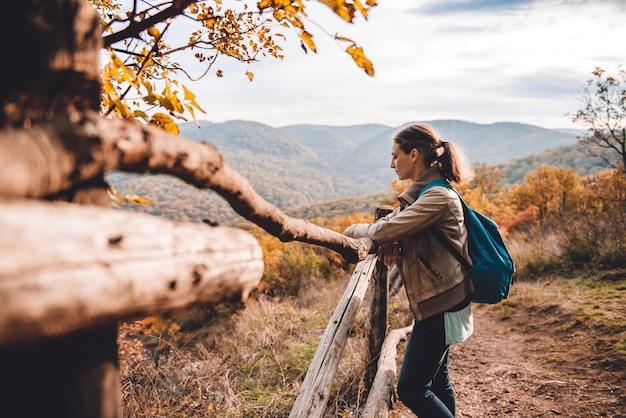 Mujer en la montaña de pie junto a la valla y disfrutar de la vista