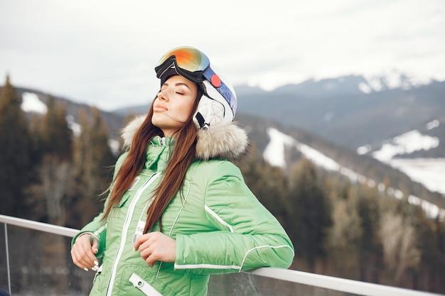 Mujer en las montañas el día de invierno. dama con uniforme de esquí.