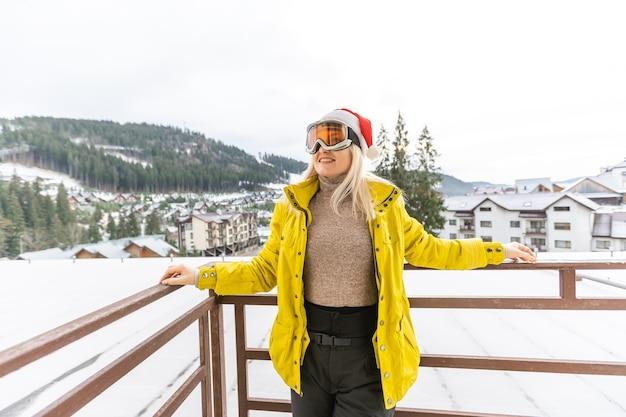Mujer en las montañas con gorro de papá noel celebrando la navidad
